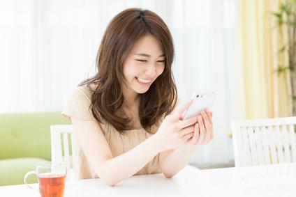 スマートフォンを操作している女性の画像